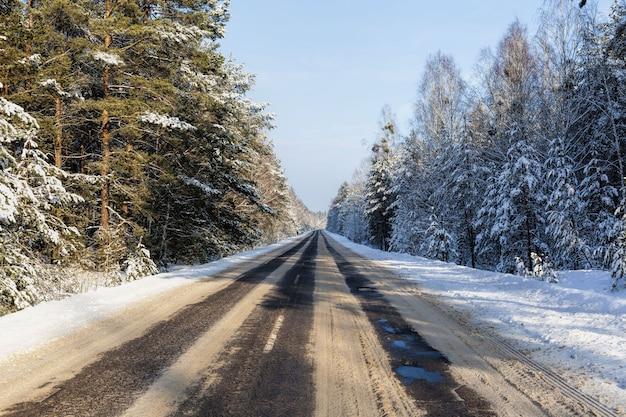 車の交通のための雪に覆われた冬の道