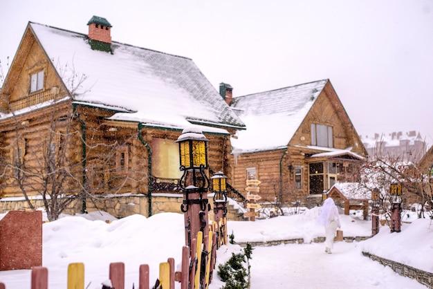 Заснеженные деревянные дома и красивый фонарь зимой в деревне