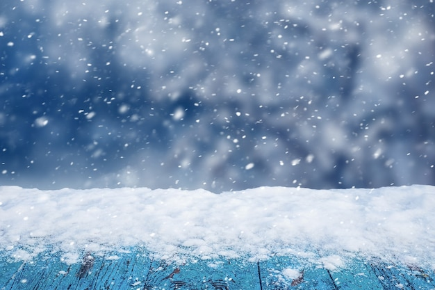 Snow-covered wooden table on blurred background during snowfall, copy space