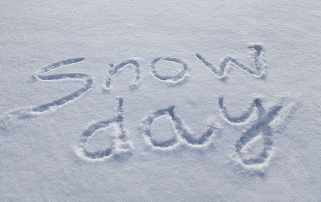 Snow day written in capital letters in fresh snowfall signifies no school