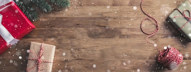 Snow flakes falling upon gift boxes on a wooden table - christmas banner with copy space
