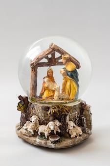 クリスマスツリーの白い背景の上の幸せな聖家族とスノードーム