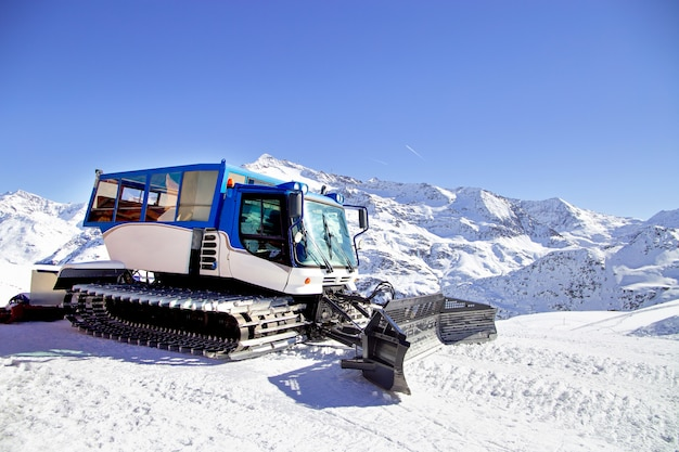 Snow grooming machine on snow hill ready for skiing slope preparations in alps, europe ski resort
