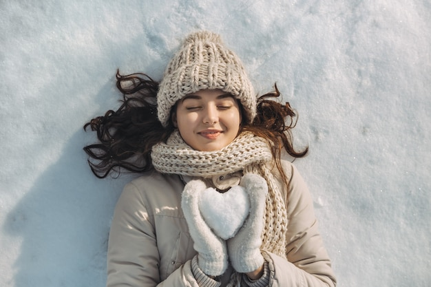 Snow heart in hands of a woman