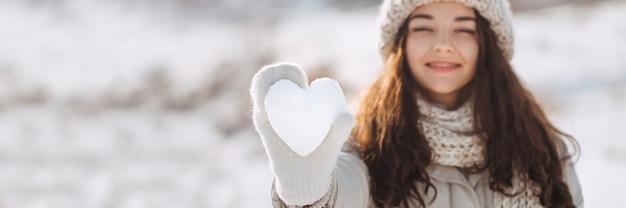 Снежное сердце в руке женщины