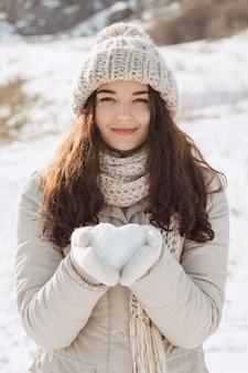Снежное сердце в руках женщины на открытом воздухе
