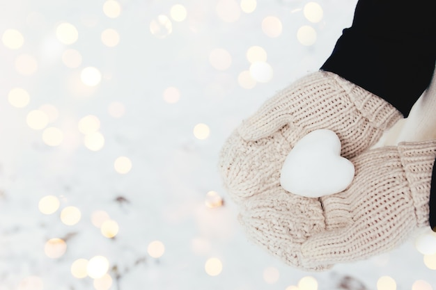 女の子の手袋をはめた手で雪の心の雪玉