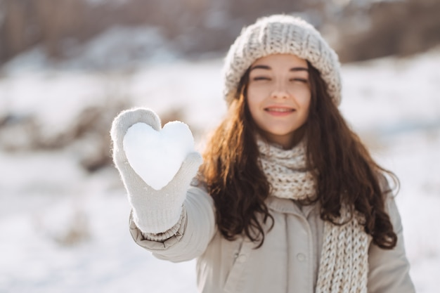 Snow heart in woman's hand outdoors