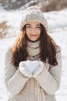 Snow heart in woman's hands outdoors