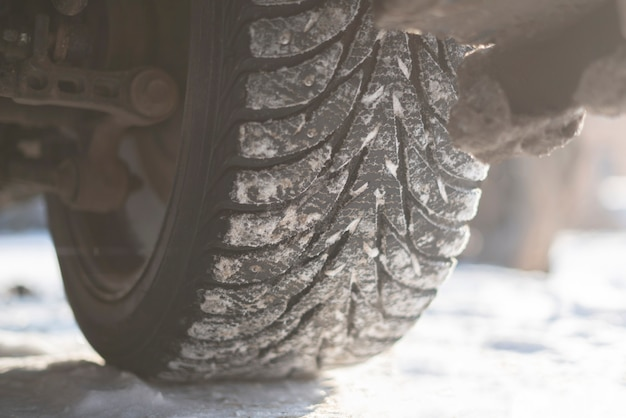 A snow and ice winter car tyres close up auto vehicle wheel