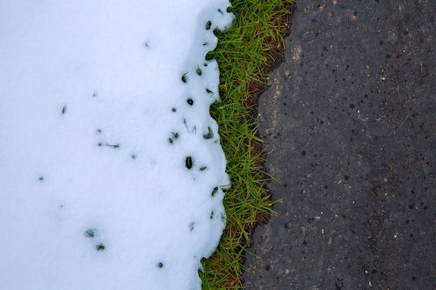 Снег в дороге с газонной травой
