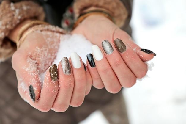 マニキュアを持つ少女の手に雪が降る