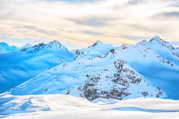 日没時の雲の高い青い山の雪の風景