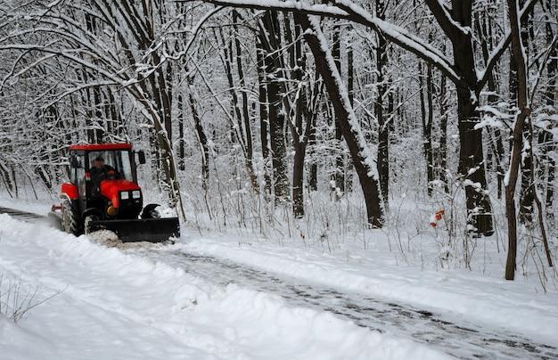 Снегоочиститель, красный трактор убирает снег от снега