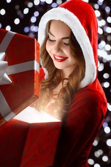 Снегурочка открывает блестящий подарок на новый год.