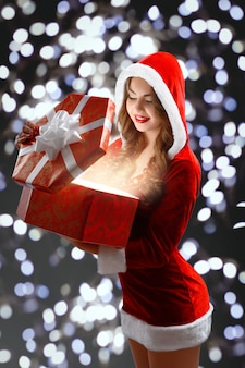 Snow maiden in red suit holding a gift for new year