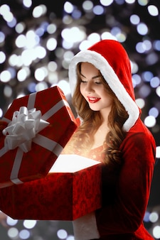Snow maiden in red suit opens a red gift for christmas and new year 2018,2019