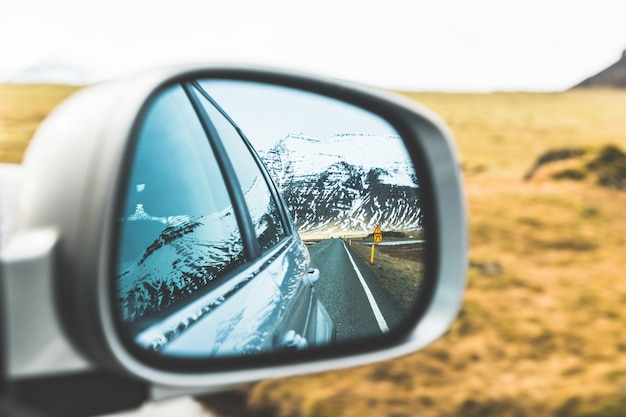Snow and mountains view on wing mirror