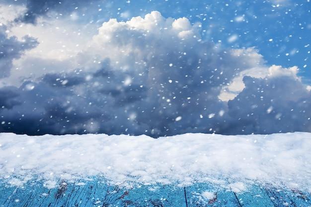 降雪時の冬の曇り空を背景に木製のテーブルに雪が降る