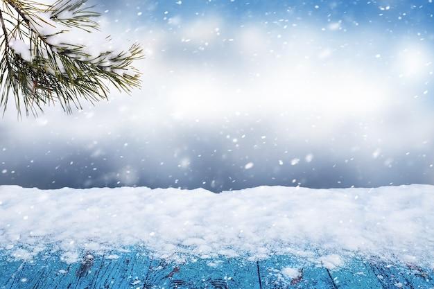 トウヒの枝を持つ抽象的な冬の背景に木製のテーブルに雪が降る