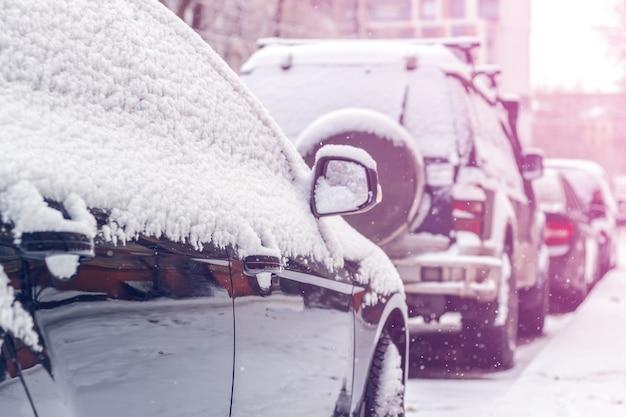 Снег на машинах после снегопада. зимняя городская сцена. тонированный