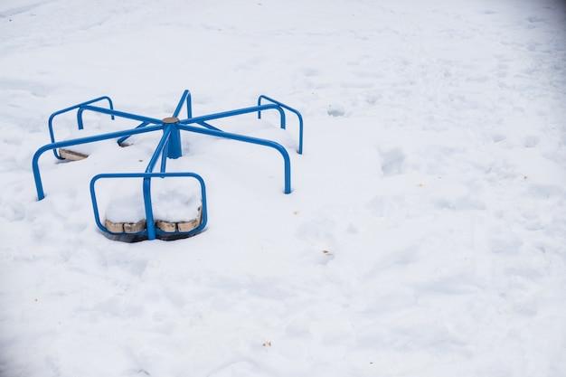 Снег на детских качелях после сильного снегопада. карусель качели. городская сцена городской жизни в зимнее время в снежную бурю. зима на детской площадке. детская площадка под снегом