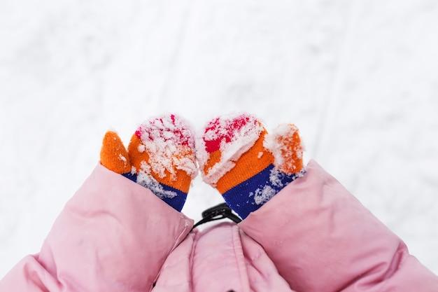 Снег на варежках или перчатках. детские руки держатся за руки в снегу.