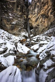 フレンチアルプスの洞窟の横にある冬の岩に雪