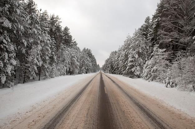 道路に雪が降る。車の痕跡が表面に印刷されました