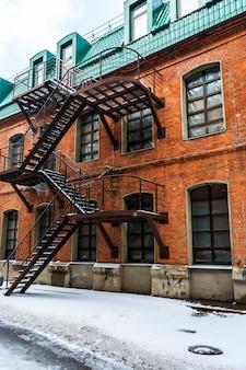 通りの雪。階段を備えたレンガ造りの家