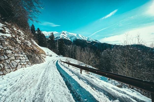 雪に覆われた山のある山の側の雪道