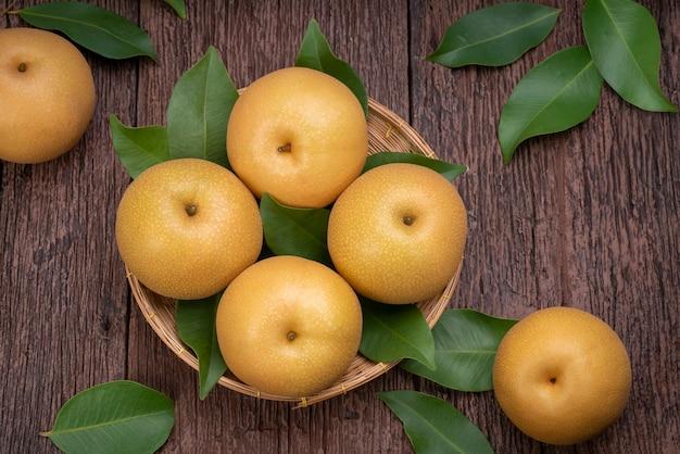 나무 배경에 있는 눈 배 또는 신고 배 바구니에 맛있고 달콤한 나시 배 과일