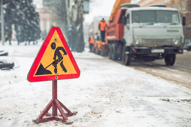 Снегоочиститель убирает снег с городской улицы. предупреждающий дорожный знак. зимняя служебная машина снегоуборочной работы. уборка снежных замерзших дорог.
