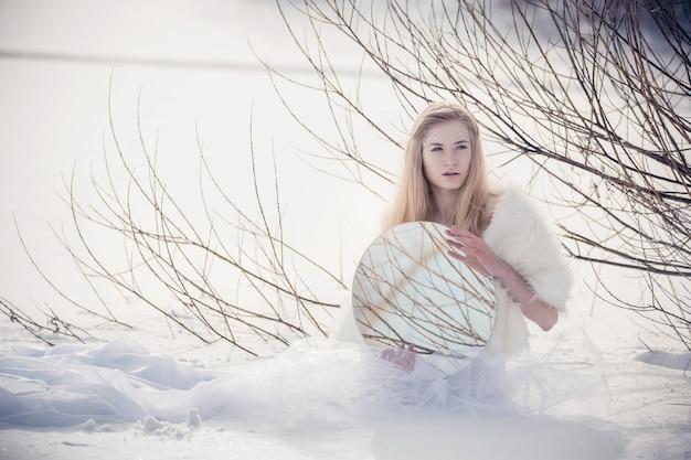 雪の女王。冬の風景の雪の中で氷の王女をイメージした少女。寒い冬の朝の女性の不思議な官能的なイメージ