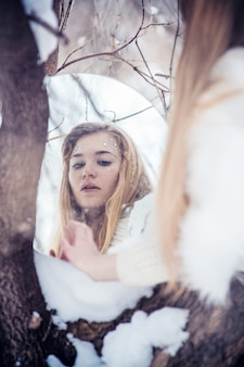 Snow queen. a young woman in the image of the ice princess in the snow on a winter landscape. mysterious sensual image of a woman on a cold winter morning