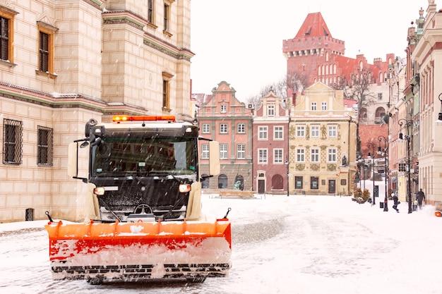 포즈난의 제설 및 거리 청소. 눈 덮인 겨울 날, 폴란드 포즈난의 구시가지에 있는 왕궁과 구시장 광장