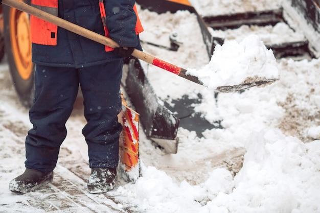 Вывоз снега по городу. работник помогает сгребать снегоочиститель.