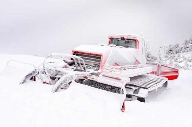 Снегоуборочная машина в снежном горном пейзаже.