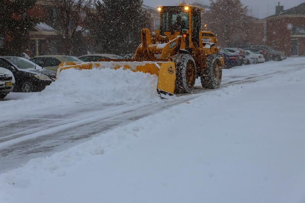 Snow-removing machine cleans the street of the city park from the snow