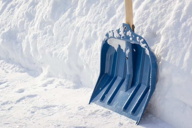 通りの歩道を掃除した後の木製ハンドル付き雪かき