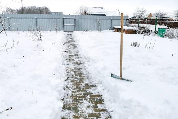 木製の柄が付いた雪かき-カントリープロットの雪の漂流の道を切り開きます。カントリーハウスの世話のための冬の雑用。除雪作業
