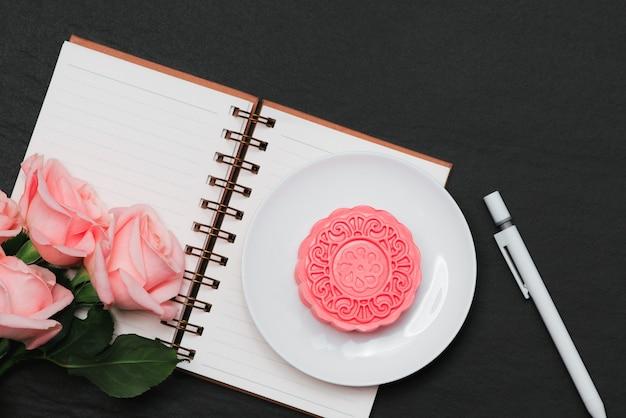 Лунный пирог из снежной кожи и розовые цветы. открытый блокнот с копией пространства.