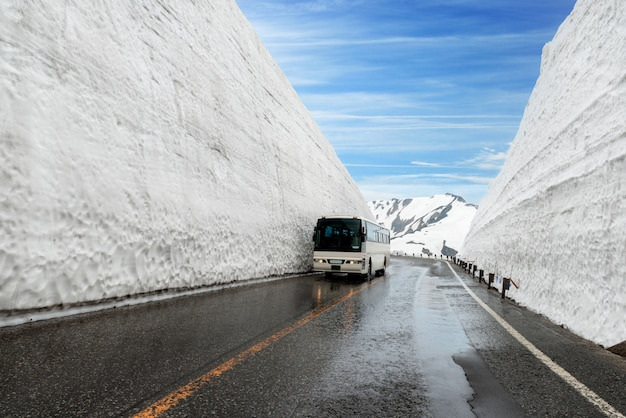 Snow wall at kurobe alpine in japan with bus for tourists on tateyama kurobe alpine route