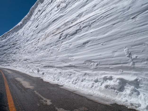 Snow wall with blue sky on the road in sunny day