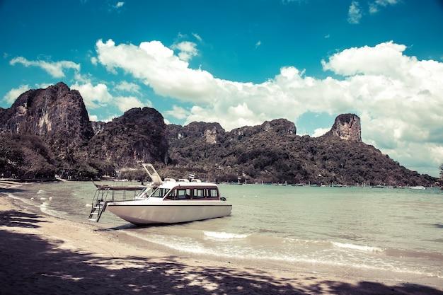 모래 해변에 정박해 있는 열대 섬의 해안에 있는 백설 공주 쾌속정