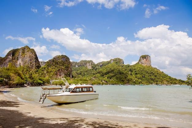 모래 해변에 정박된 열대 섬 해안에 있는 백설 공주 쾌속정