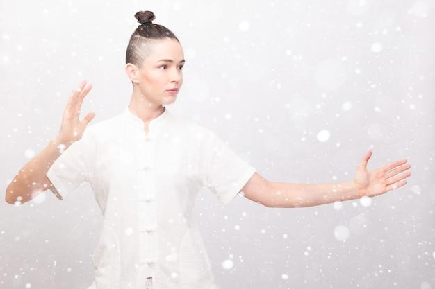 Снег, зима, рождество, фитнес, спорт, обучение и концепция образа жизни - молодая женщина делает упражнения йоги. китайский управленческий навык энергия ци на фоне снега