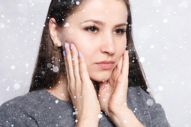 雪、冬、クリスマス、健康、人々、歯科とライフスタイルの概念-歯の問題。歯の痛みを感じる女性。雪の背景に強い歯の痛みに苦しんでいる美しい悲しい少女のクローズアップ