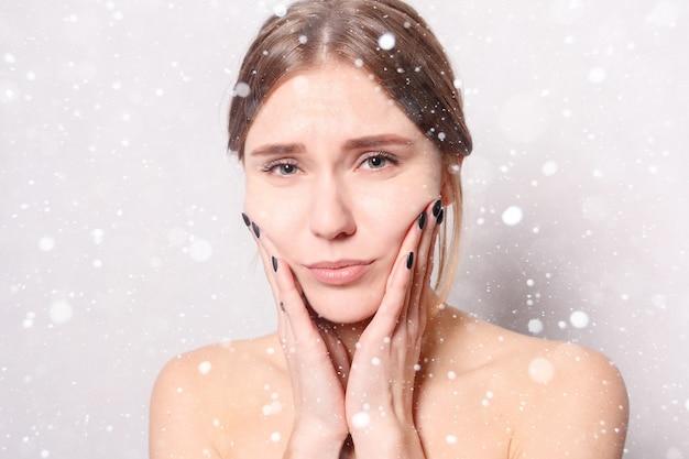 雪、冬、クリスマス、健康、人々、歯科とライフスタイルの概念-歯の問題。歯の痛みを感じる女性。強い歯の痛みに苦しんでいる美しい悲しい少女のクローズアップ。雪の背景の上
