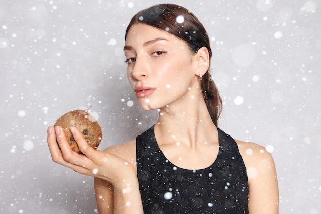 눈, 겨울, 크리스마스, 건강, 사람, 음식 및 미용 개념-눈 배경 위에 그녀의 손에 코코넛과 가벼운 자연 메이크업과 완벽한 피부를 가진 아름다운 어린 소녀